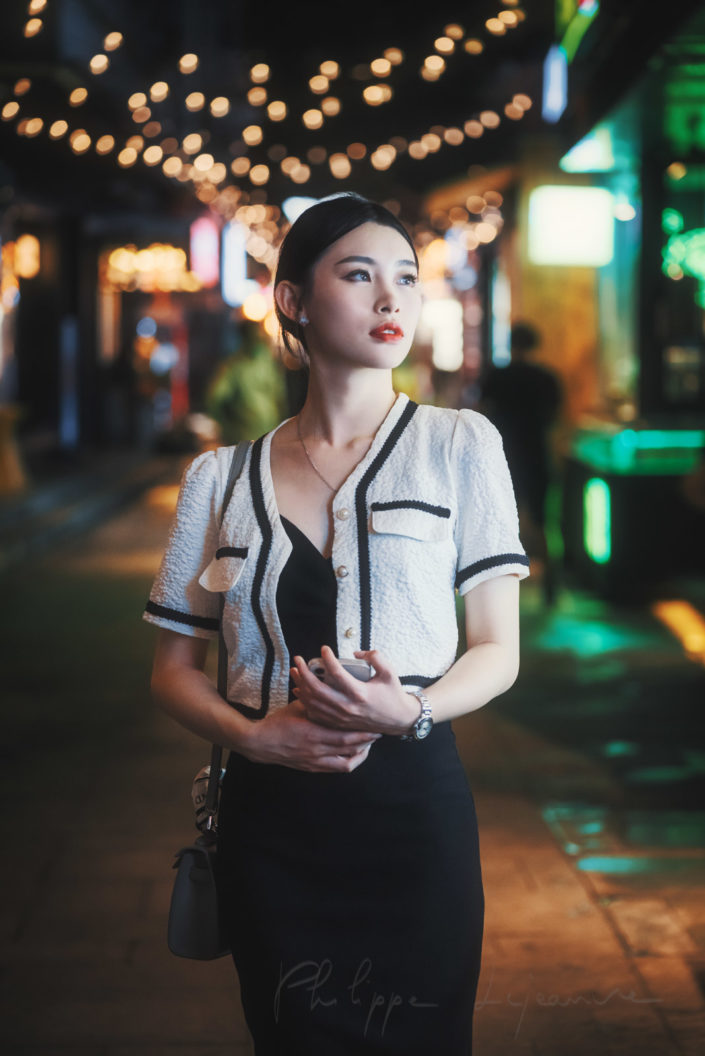 Young chinese woman standing in the street with neon lights at night in Chengdu, Sichuan province, China