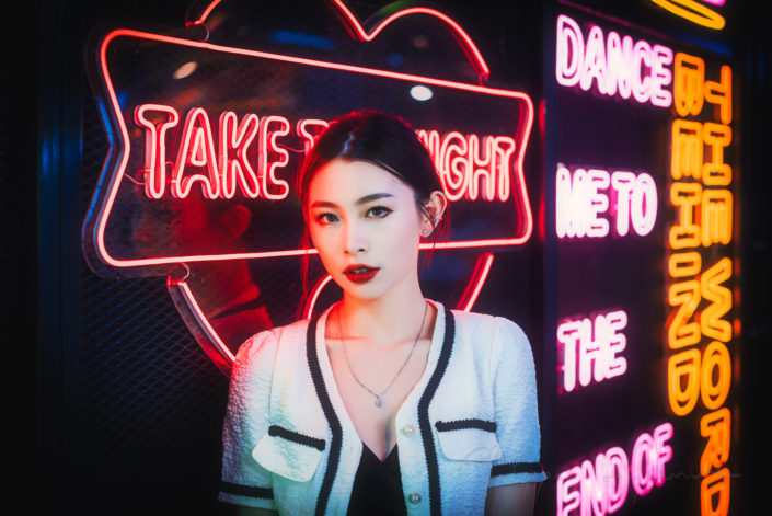 Young chinese woman standing next to neon lights in Chengdu, Sichuan province, China