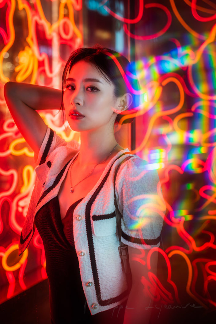 Young chinese woman standing next to red neon lights in Chengdu, Sichuan province, China