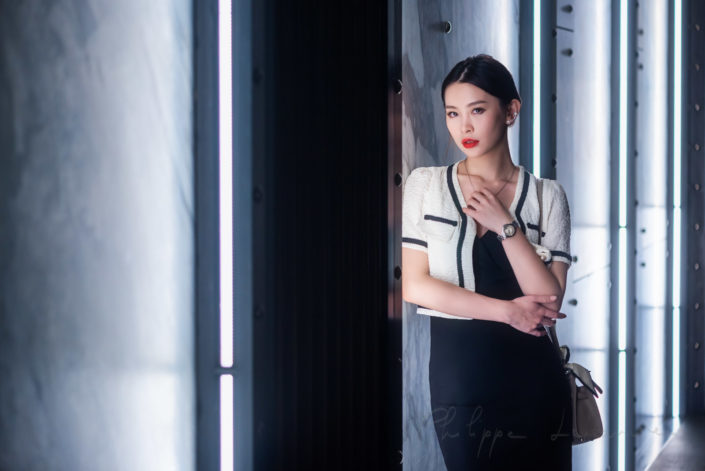 Young chinese woman standing next to white neon lights in Chengdu, Sichuan province, China