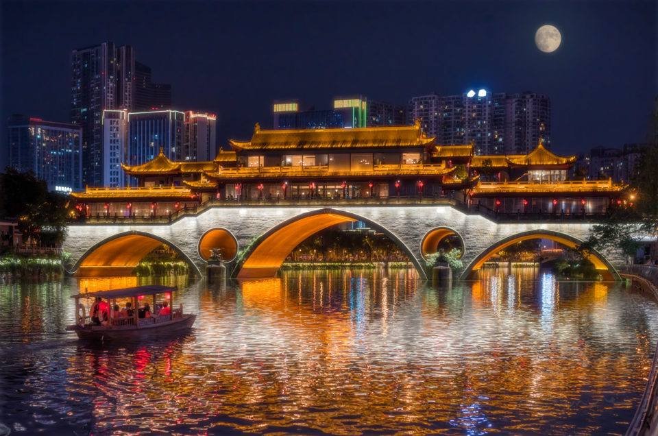 Anshun bridge illuminated at night with full moon. A chinese ancient little boat with red chinese lanterns is sailing on the Jinjiang river for the mid-autumn moon festival