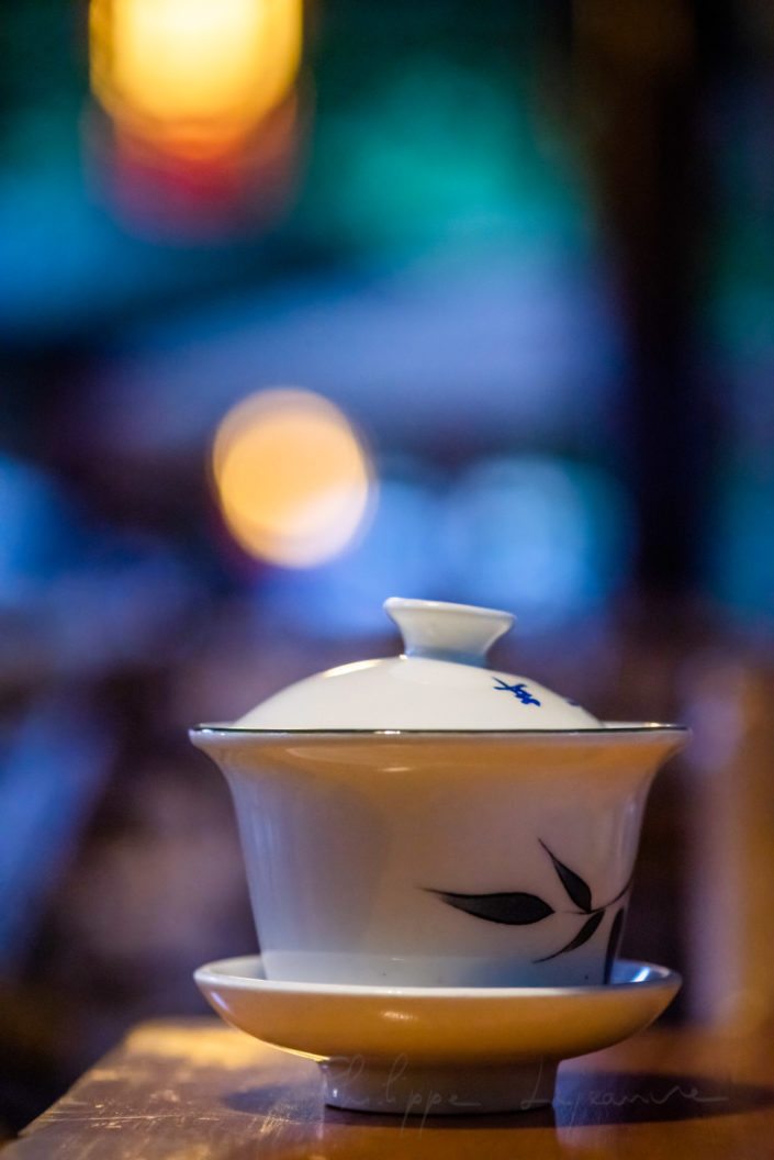 Chinese teacup against colorful blurred background in Heming ancient teahouse, People' s park, Chengdu, Sichuan province, China