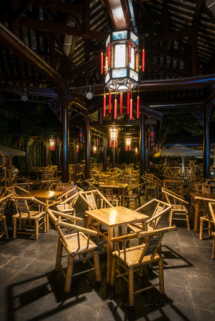 Heming ancient teahouse illuminated at night in People' s park with empty bamboo chairs in the foreground, Chengdu, Sichuan province, China
