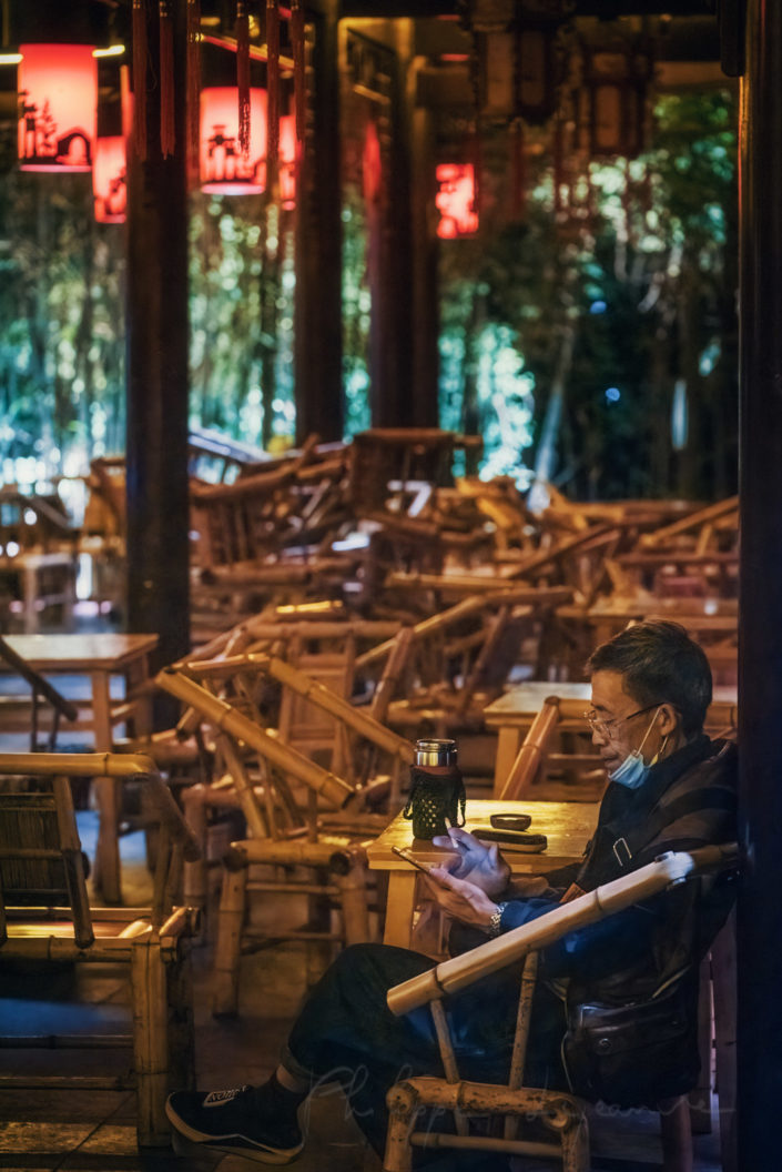 One man having tea in Heming ancient teahouse illuminated at night in People' s park, Chengdu, Sichuan province, China