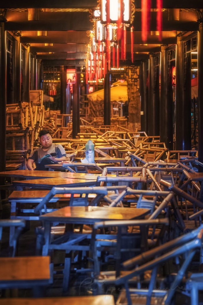 One man having tea in Heming ancient teahouse illuminated at night in People' s park,, Chengdu, Sichuan province, China