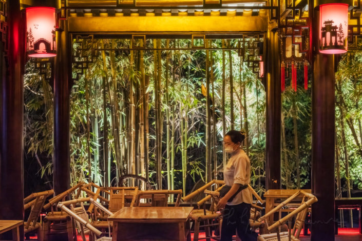 Waitress in Heming ancient teahouse illuminated at night in People' s park, Chengdu, Sichuan province, China