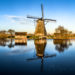 Windmill reflecting in water in Kinderdijk, Rotterdam, Netherlands
